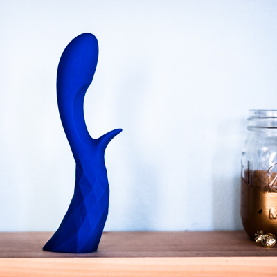 royal blue L'Amourose Prism VII rabbit vibrator standing upright on a light wood shef next to a gold painted mason jar against a light blue blackground and