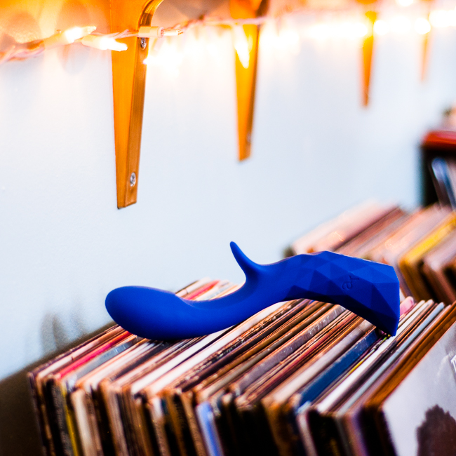royal blue rabbit vibrator resting on top of a stack of records under a row of twinkle lights
