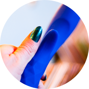 crop of the royal blue L'Amourose Prism VII external arm next to a person's thumb with teal nail polish for size comparison