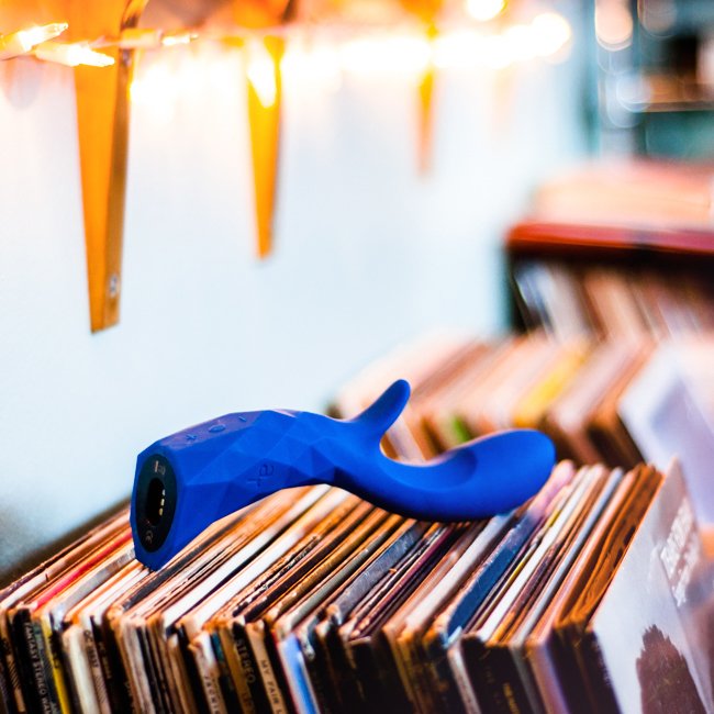 royal blue L'Amourose Prism VII rabbit vibrator resting on top of a stack of records under a row of twinkle lights